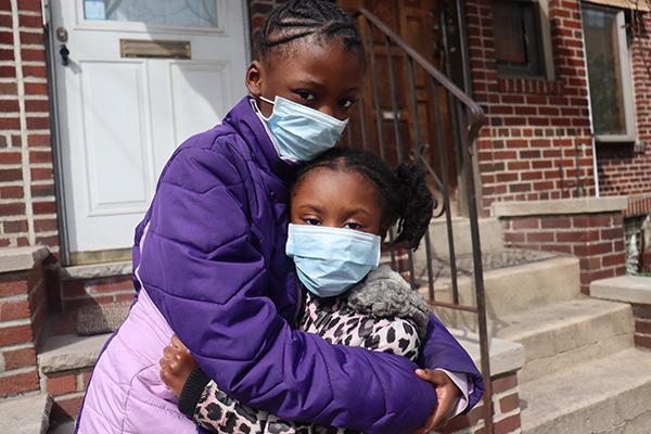 2 girls wearing masks and hugging